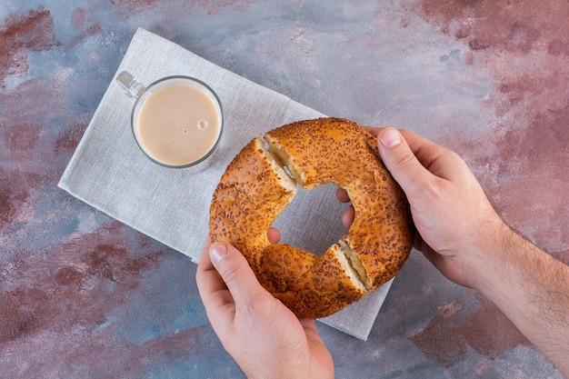 Una taza de café con leche y bagel turco en rodajas sobre la superficie de mármol