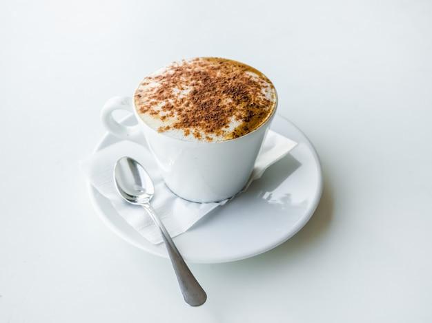 Taza de café con leche blanca en mesa blanca.