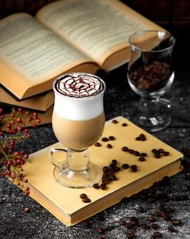 Una taza de café con leche caliente con espuma y un patrón