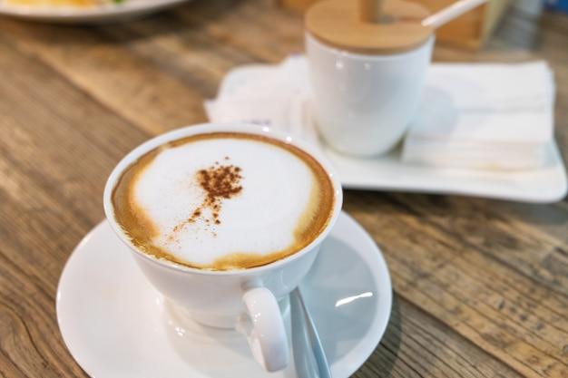 Una taza de café con leche caliente con leche (café con leche o café capuchino) en la mesa de madera