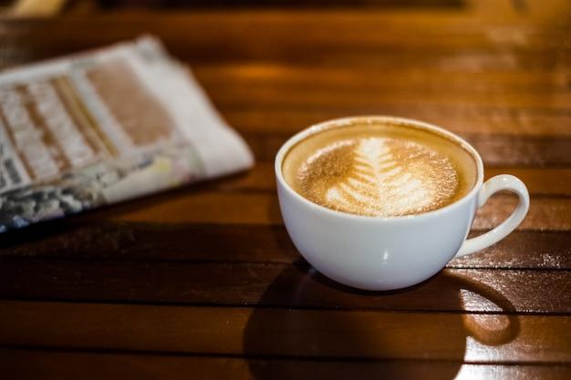 Taza de café con leche caliente con periódico en la mesa de madera