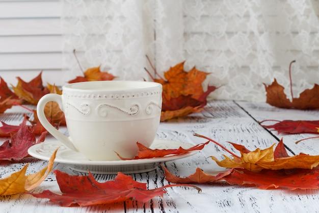 Taza de café con leche y coloridas hojas de otoño