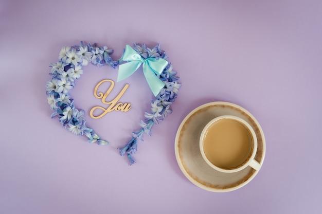 Taza de café con leche y corazón hecho de las flores del jacinto en fondo púrpura.