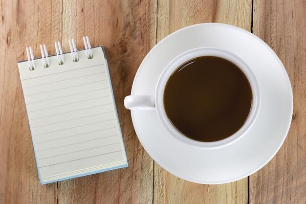Taza de café con leche y cuaderno.