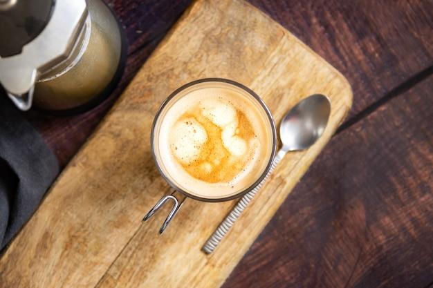 Taza de café con leche y cucharadita de mesa de madera y cafetera italiana. vista superior