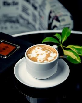 Una taza de café con leche con estampado de oso