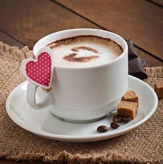 Taza de café con leche en el fondo de madera vieja