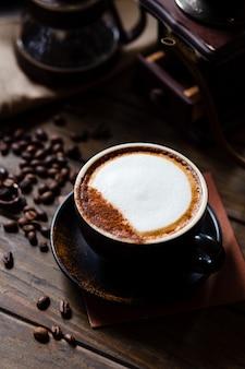 Taza de café con leche y granos de café con gotero de café en la mesa de madera.