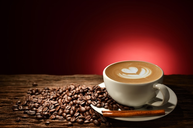 Taza de café con leche y granos de café sobre fondo marrón rojizo