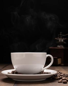 Taza de café con leche, granos de café tostados, molinillo sobre fondo de mesa de madera