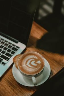 Taza de café con leche junto a una computadora portátil