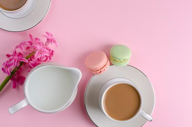 Taza de café con leche, macarrones, tarro de leche en rosa pastel