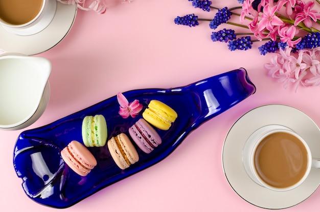 Taza de café con leche, macarrones y tarro de leche en rosa pastel