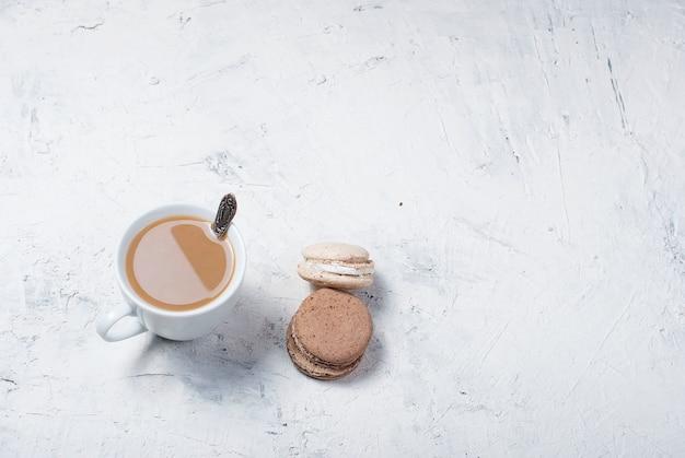 Taza de café con leche y macarrones.