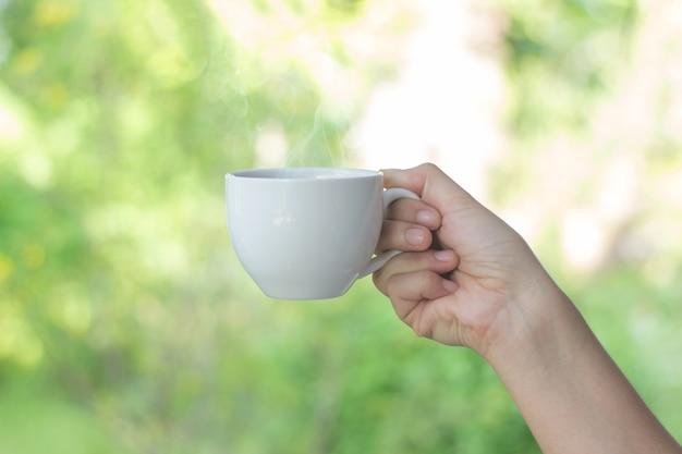 Taza de café con leche en la mano desenfoque de fondo, las mujeres jóvenes que toman café
