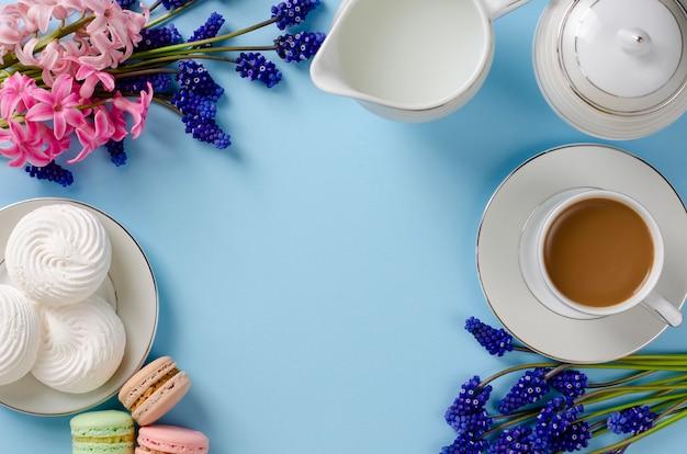 Taza de café con leche, merengues blancos, macarons, tarro de leche.