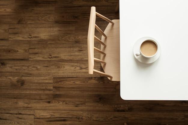 Taza de café con leche en la mesa blanca cerca de la silla de diseño y piso de madera