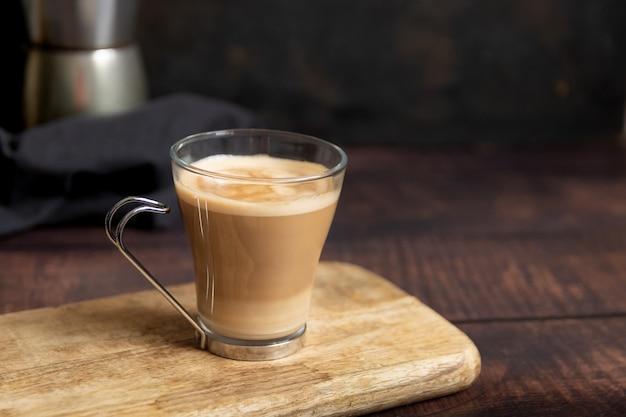 Taza de café con leche en la mesa de madera y cafetera italiana en el fondo