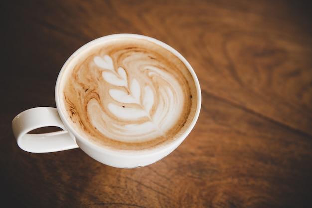 Taza de café con leche en la mesa de madera en cafetería cafetería