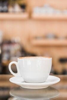 Taza de café con leche en un mostrador de cristal reflectante