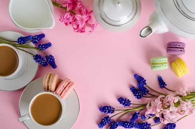 Taza de café con leche o café con leche, macarrones y tarro de leche en rosa pastel