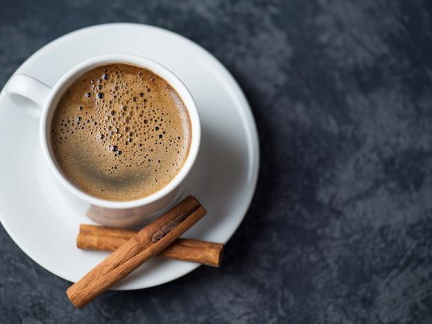 Taza de café con leche y rodajas de pollo sobre superficie oscura de piedra