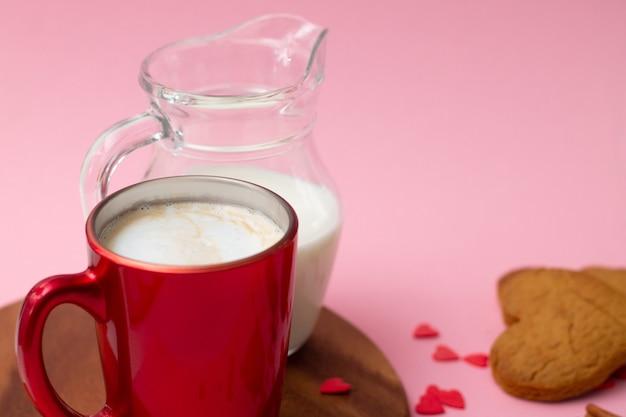 Taza de café con leche roja y jarra de leche con galletas en forma de corazón y corazones rojos