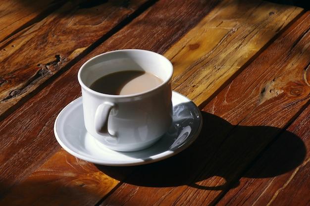 Una taza de café con leche bajo el sol de la mañana.