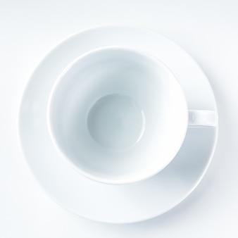 Taza de café con leche vacía sobre fondo blanco.