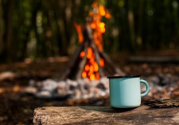 Taza de café y leña borrosa en el fondo