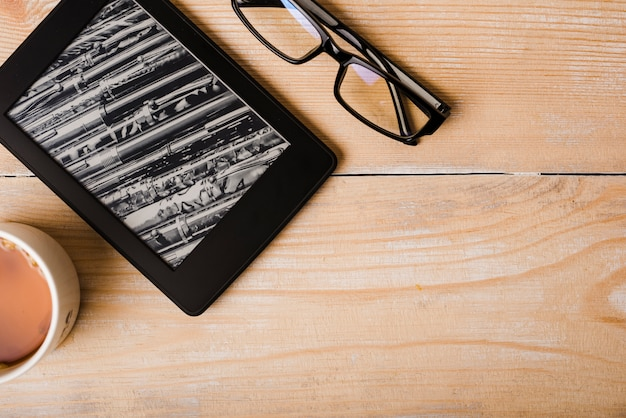 Taza de café; lentes y lector de libros electrónicos en el escritorio de madera.