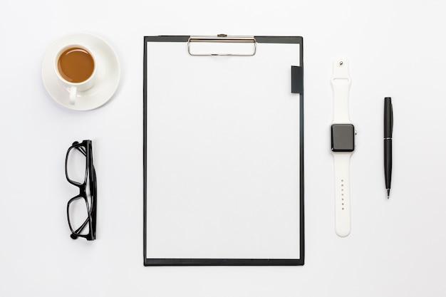 Taza de café, lentes, reloj inteligente, bolígrafo y portapapeles de papel en blanco en el escritorio blanco