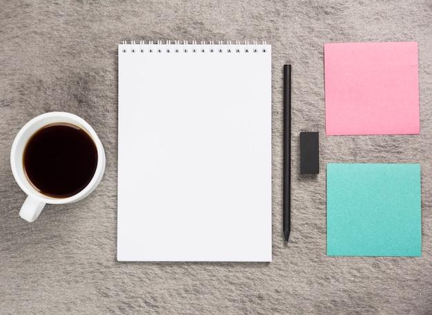 Taza de café; libreta espiral en blanco; borrador negro; lápiz y nota adhesiva en escritorio gris.