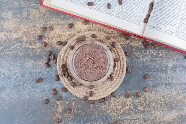 Una taza de café con libro abierto y granos de café sobre fondo de mármol. foto de alta calidad