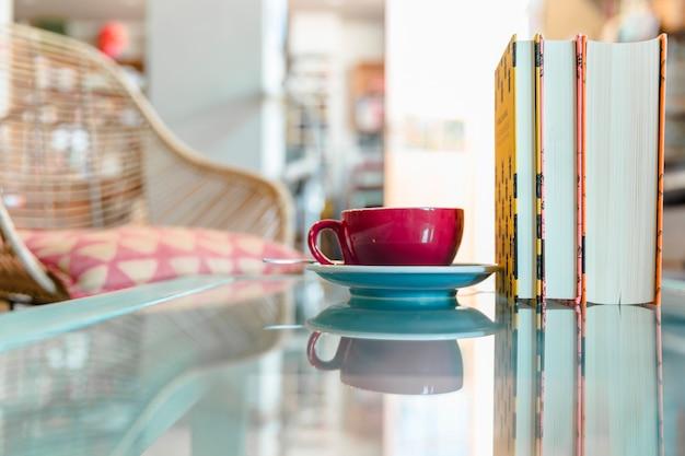 Taza de café y libro cerrado en la mesa de vidrio reflectante