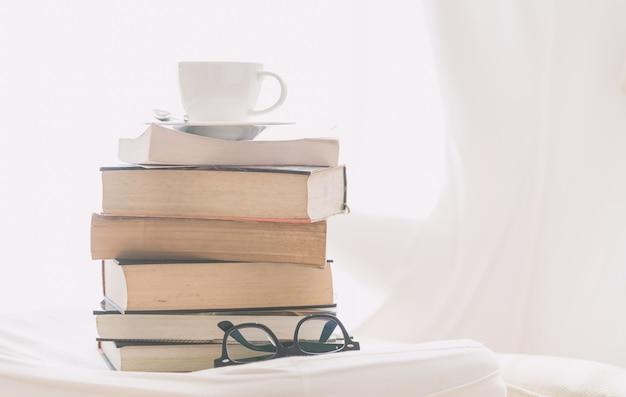 Taza de café con libro y gafas.