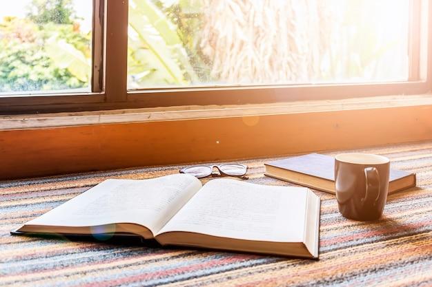 Taza de café y libro junto a la ventana con suave enfoque en el fondo. sobre la luz
