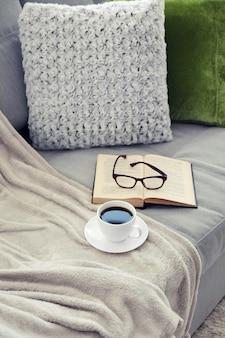 Taza de café con libro en el sofá en la habitación