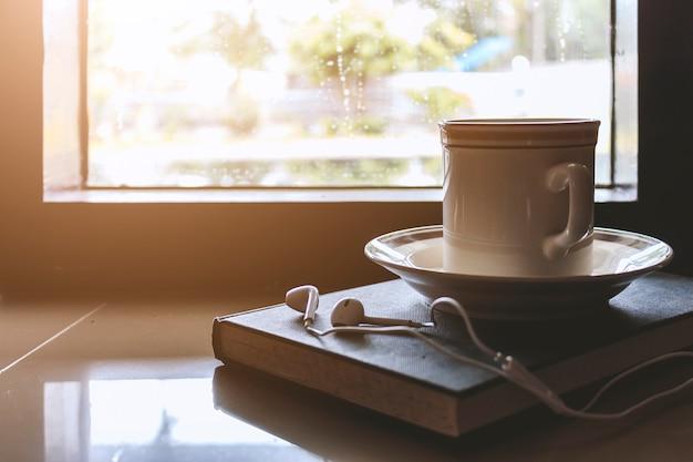 Taza de café en el libro por la ventana en un día lluvioso con suave-foco en el fondo.