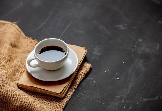 Taza de café y libro vintage sobre una mesa oscura