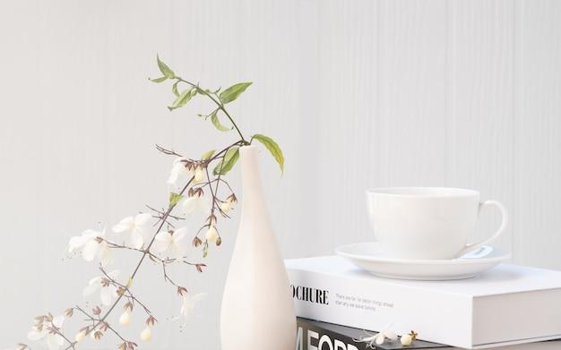 Taza de café en libros en blanco y negro simulacro y hermosa flor en florero moderno en mesa de hormigón con fondo de madera blanca