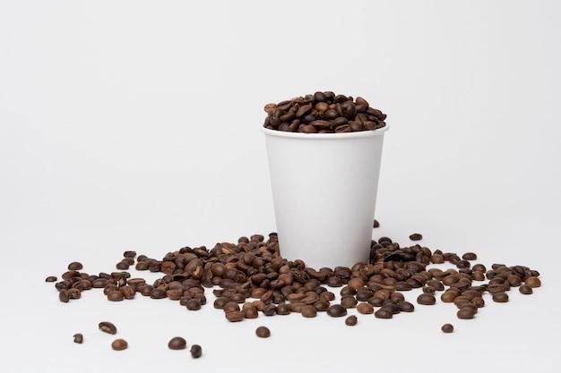 Taza de café llena de granos de café.