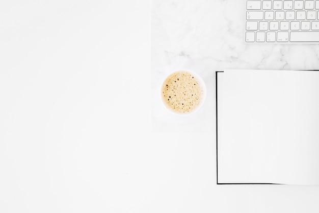 Taza de café para llevar; cuaderno en blanco y teclado en el escritorio contra el fondo blanco