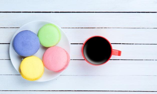 Taza de café y macarons sobre fondo blanco de madera