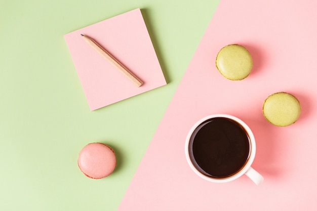 Taza de café con macarrones sobre fondo pastel