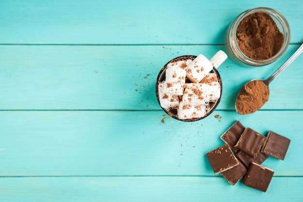 Una taza de café con malvavisco, una bufanda azul tejida, barra de chocolate y cacao sobre fondo de madera verde. bebidas y dulces.