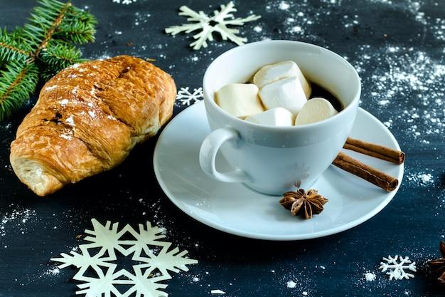 Taza de café con malvaviscos, croissant, canela y anís estrellado.