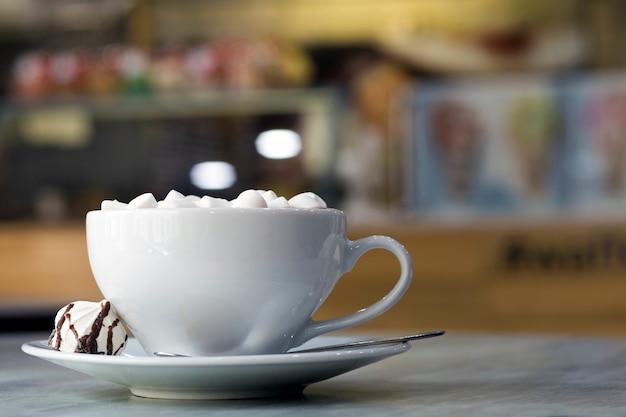 Taza de café con malvaviscos en plato de porcelana sobre fondo bokeh interior colorido borrosa.