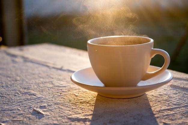 Taza de café por la mañana al aire libre al amanecer.