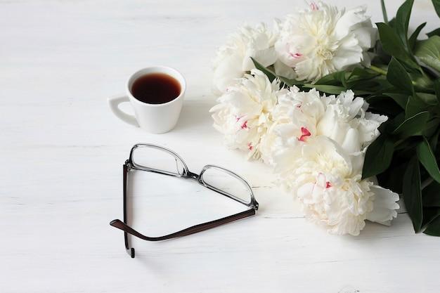 Taza de café de la mañana, gafas y flores de peonías blancas en mesa de madera blanca